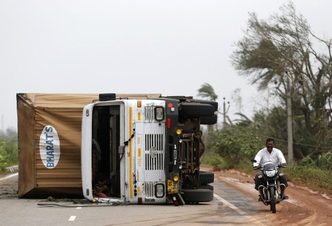 A man rides his motorbike past an overturned vehicle after Cyclone Phailin hit Gopalpur in Ganjam district in Odisha