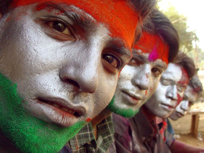 Indians sit with their faces painted with the colours of the Indian national flag as they celebrate Holi in the central Indian city of Bhopal