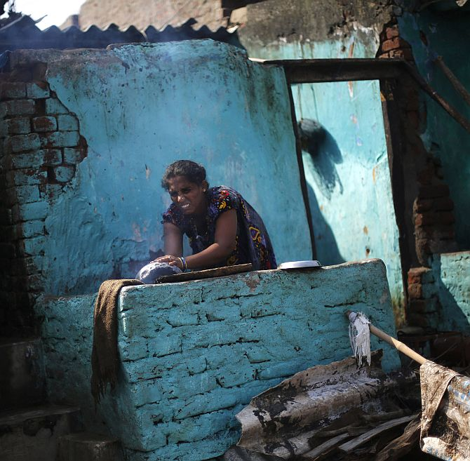 A woman cooks food outside her partially damaged house at the cyclone-hit Gopalpur village, in Ganjam district
