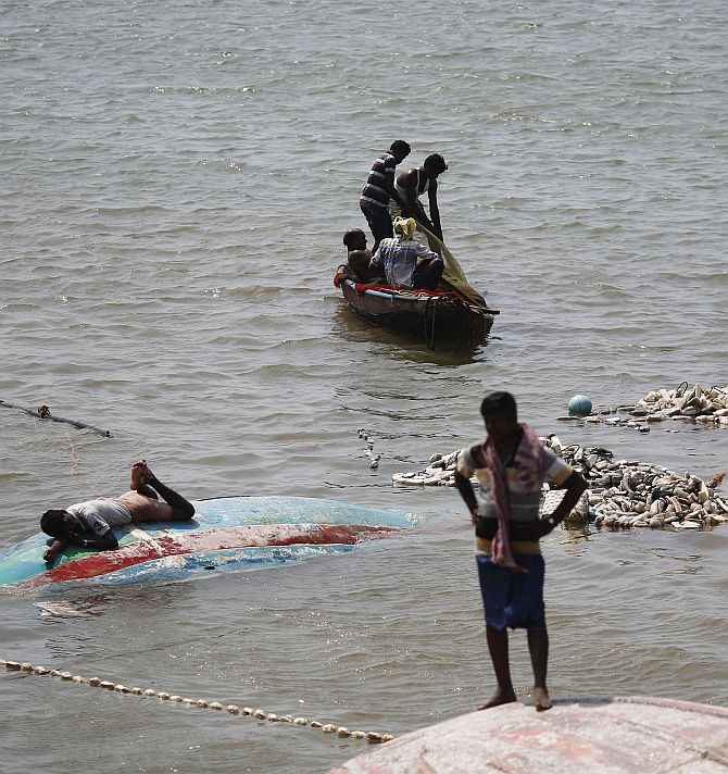 A fisherman lies on his overturned boat as others take out their fishing nets from the sea after Cyclone Phailin hit Gopalpur port in Ganjam district