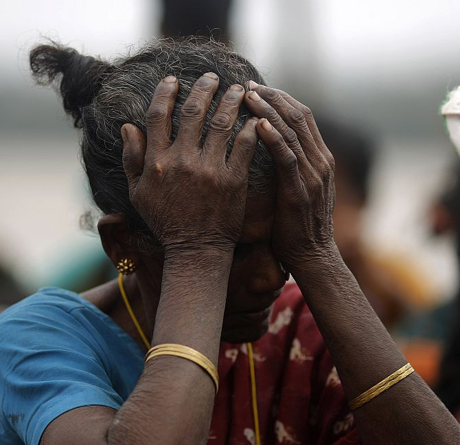 A woman holds her head after Cyclone Phailin hit Sunapur village in Ganjam