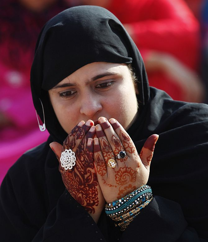 A Muslim woman with henna tattoos on her hands, attends a mass prayer for Eid al-Adha