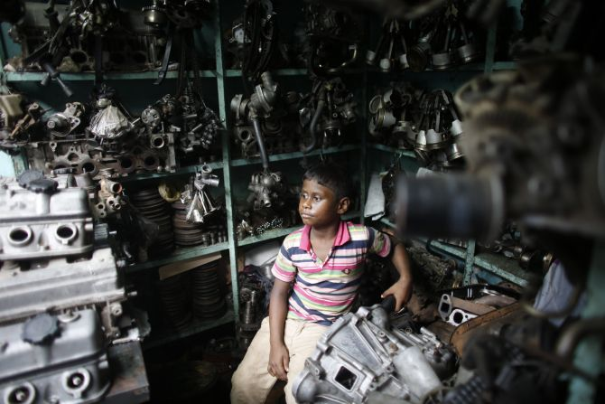 Sujon, 7, sits inside a vehicle spare parts store, as he works in Dholaikhal, Dhaka