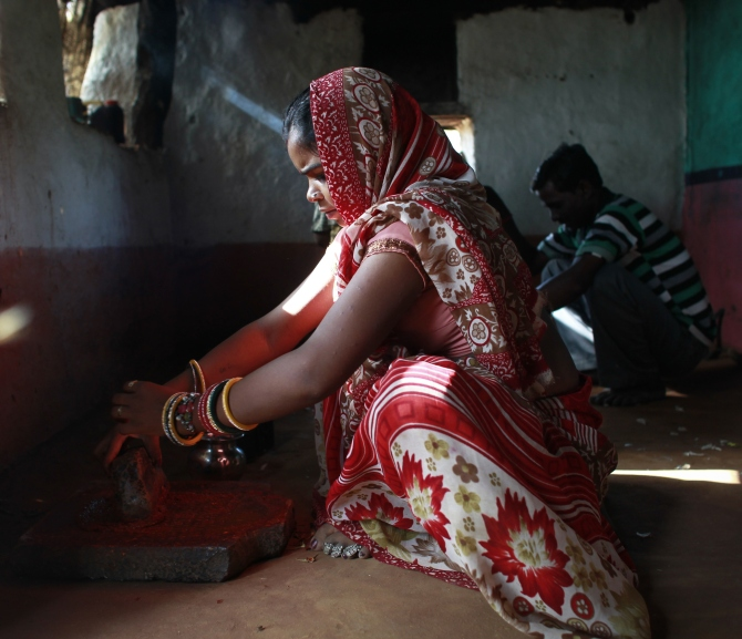 Krishna, 13, grinds spices inside the kitchen at her house in a village