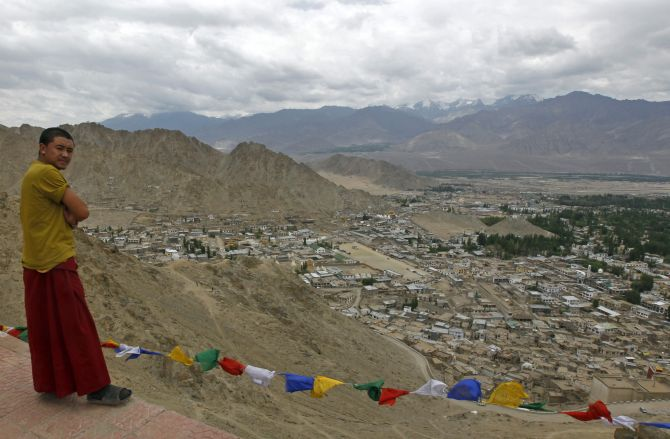 A Buddhist monk stands on a pathway overlooking Leh city in Ladakh.