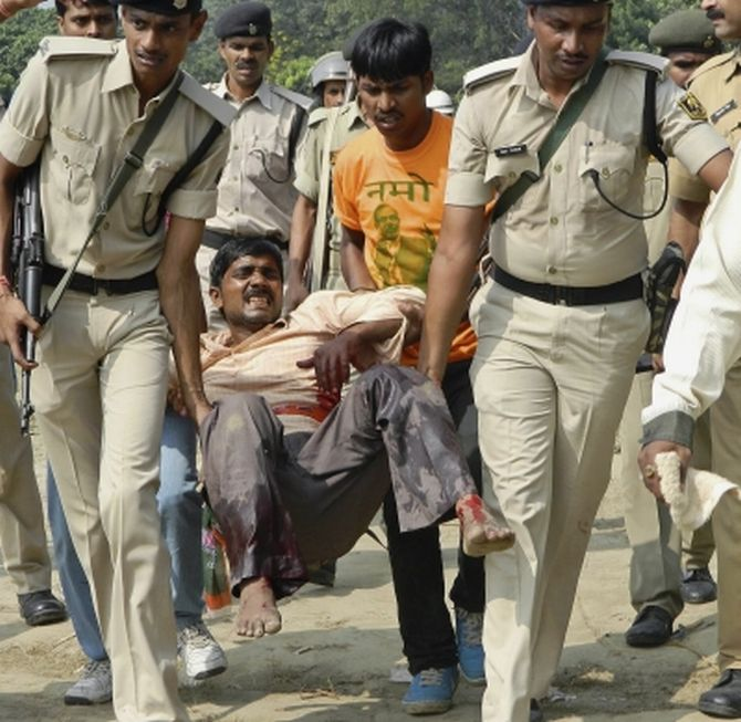 Police personnel carrying an injured man after serial blasts rocked Patna's Gandhi maidan during Modi's rally on Sunday