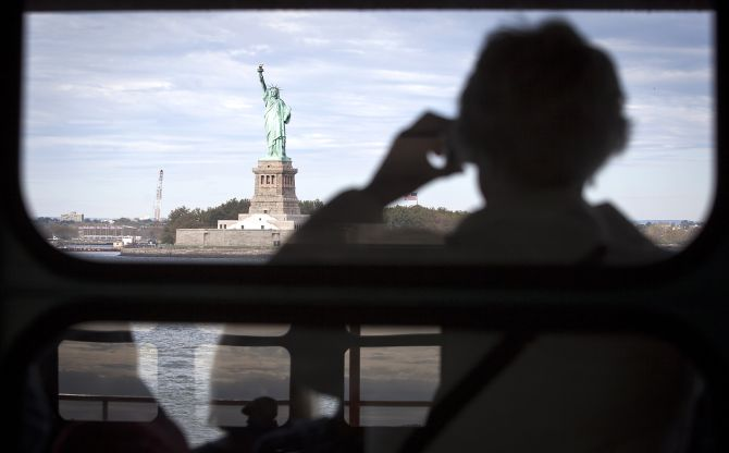 The Statue of Liberty is pictured from the Staten Island Ferry as people are reflected in windows in New York