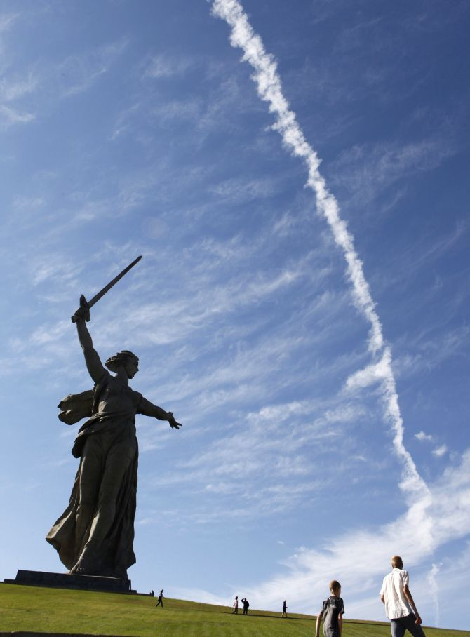 People walk by 'The Motherland Calls' monument in Russia's southern city of Volgograd