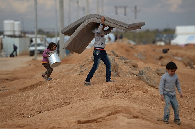 A boy carries a mattress as Syrian refugees go about their daily business in the Za'atari refugee camp in Mafraq, Jordan