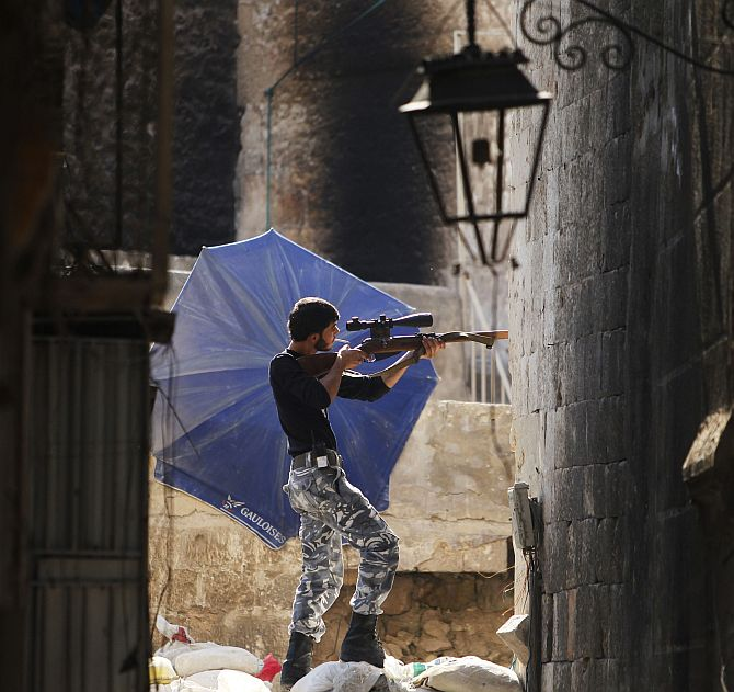 A Free Syrian Army fighter aims his weapon as he takes a defensive position in the old city of Aleppo