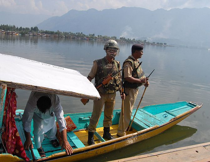 Security personnel on a shikara on Dal Lake