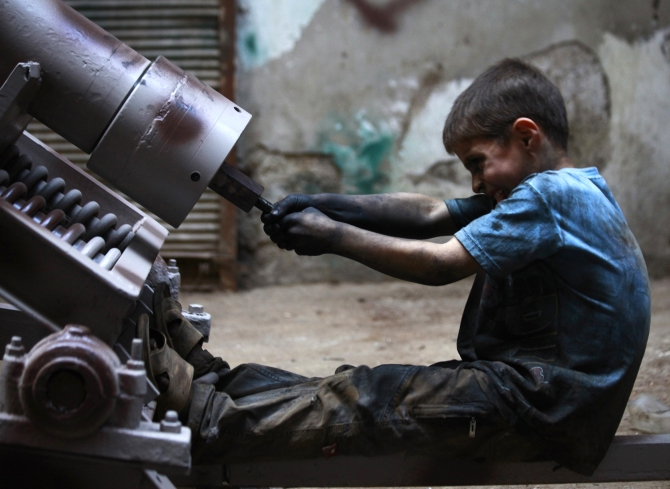 Issa, 10 years old, fixes a mortar launcher in a weapons factory of the Free Syrian Army in Aleppo