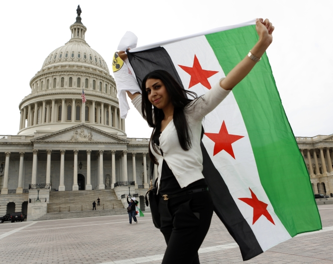 An anti-Assad protester carries the Syrian freedom flag in front of the US Capitol in Washington