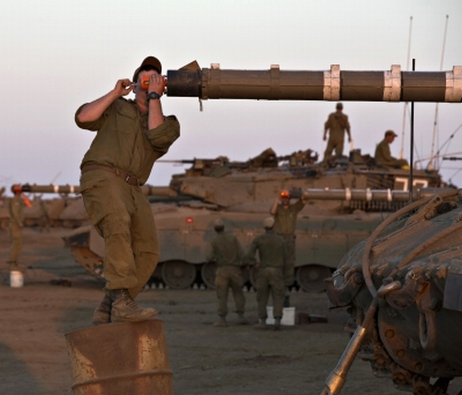 An Israeli soldier adjusts sights on a tank during a drill in the Israeli-occupied Golan Heights amid the Syria crisis