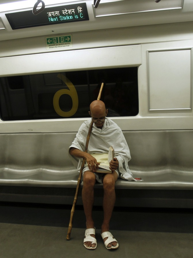 Mahesh Chaturvedi, 63, who dresses up like Mahatma Gandhi, reads a copy of the Bhagavad-Gita in the Delhi metro train.