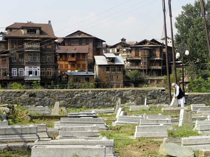 A Kashmiri prays at a grave in Zainkadal, Srinagar