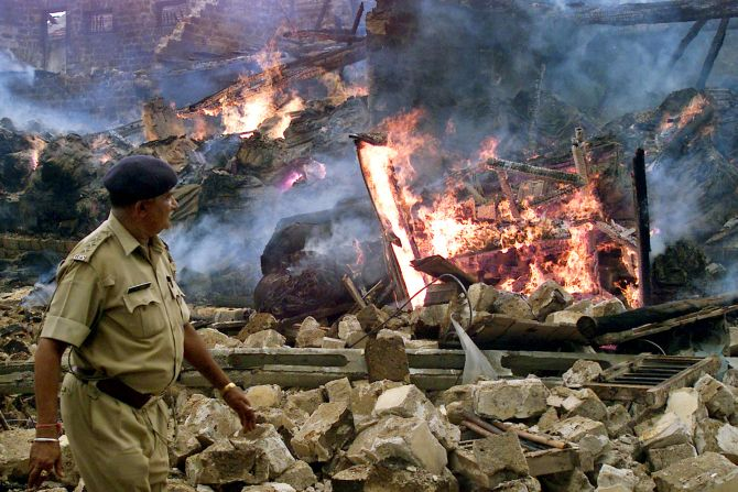 A police officer walks past flames at a building burnt by an angry mob in Veraval during the 2002 Gujarat riots.