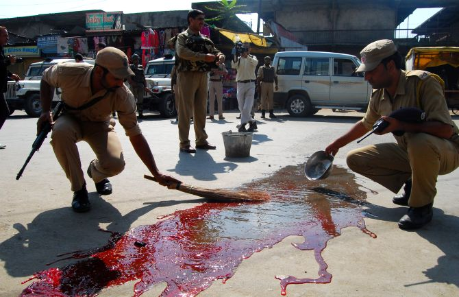 Security personnel wash the blood of the CISF jawans who were attacked in Srinagar