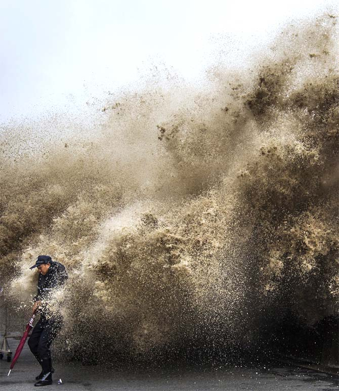 A man dodges tidal waves under the influence of Typhoon Usagi in Hangzhou, Zhejiang province