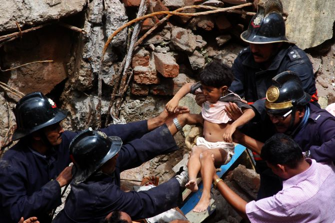 Firefighters rescue a child at the building collapse site in south Mumbai