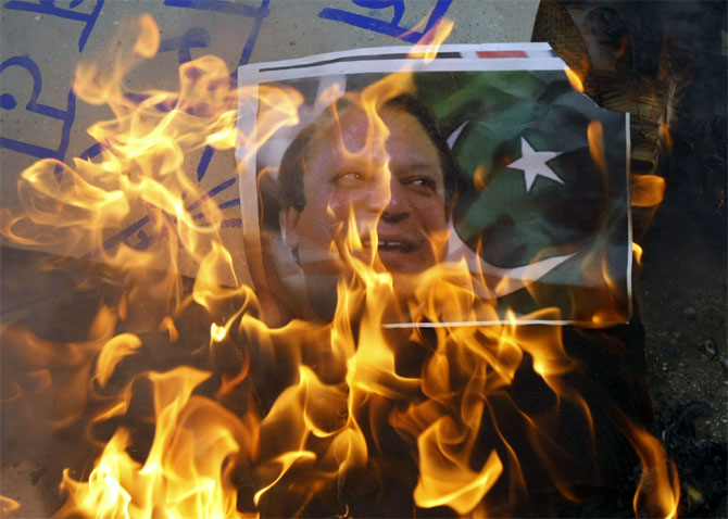 Protesters burn a poster of Pakistan Prime Minister Nawaz Sharif in Ahmedabad.