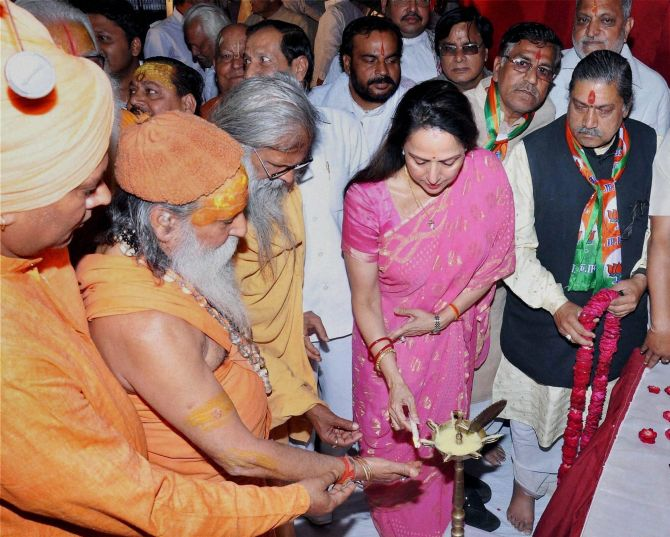 BJP Candidate and Bollywood actress Hema Malini lighting lamp along with priests during her election campaign in Mathura on Monday
