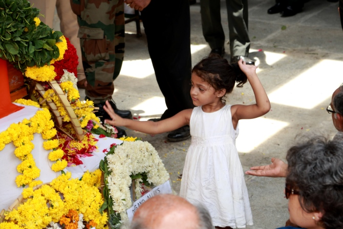 Arshea, 3, the major's daughter, stands near her father's coffin
