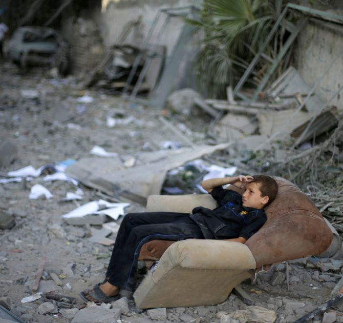 A Palestinian boy sits on a sofa outside his family's house, which witnesses said was damaged in an Israeli air strike, in Gaza City.