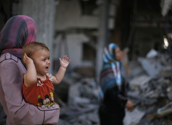 A Palestinian woman holds her daughter as she looks at the wreckage of her house in Beit Hanoun town, which witnesses said was heavily hit by Israeli shelling and air strikes during Israeli offensive, in the northern Gaza Strip.