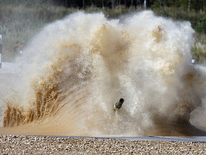 A tank drives through a water obstacle on the course of the Tank Biathlon world championship in Alabino outside Moscow