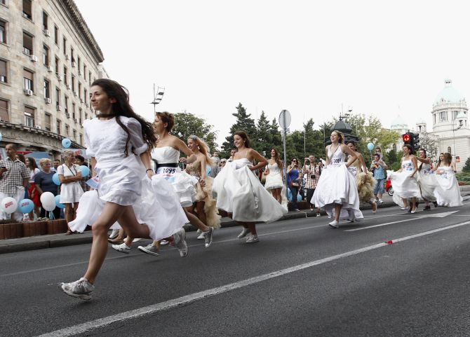 Women dressed in bridal gowns spring during the annual Bridal race in central Belgrade.