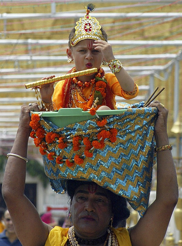 A devotee carries a child dressed as Hindu god Krishna in a basket at the Durgiana temple during the celebrations of Janmashtami in Amritsar