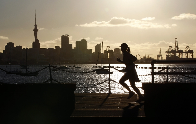 A jogger runs along the seawall in Auckland, with the city skyline in the background.