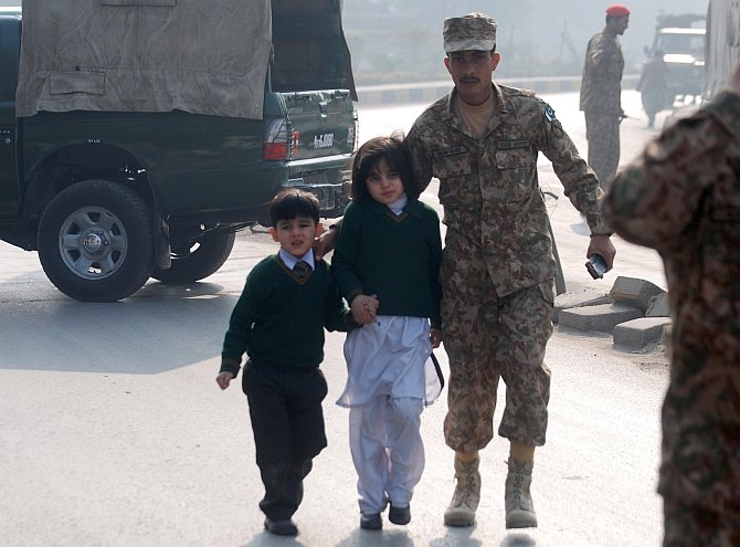 A soldier escorts children from the Army Public School that came under attack from Taliban terrorists in Peshawar. Photograph: Khuram Parvez/Reuters