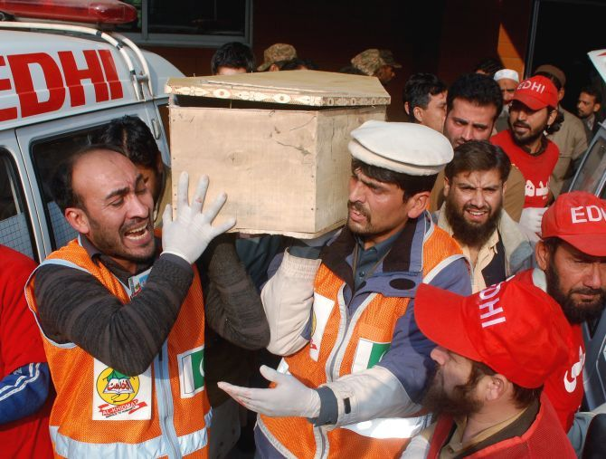 Rescue workers and family members carry the coffin of a student killed during the attack on the Army Public School in Peshawar