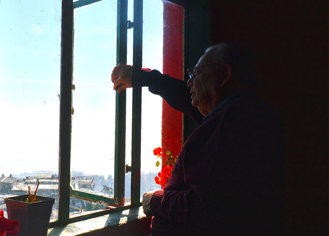 Ruskin Bond stands beside the window in his room