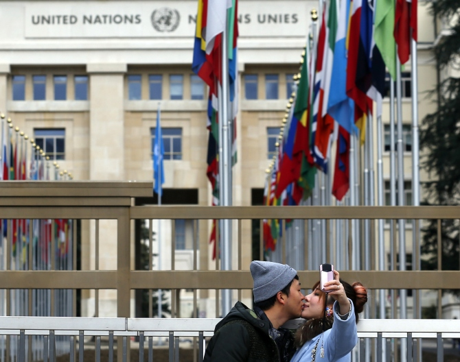 A couple takes a selfie in front of the United Nations European headquarters in Geneva.