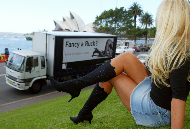 A brothel promotions team member poses for a photograph at Circular Quay in Sydney before a truck bearing the words Fancy a Ruck sets off on a drive through city streets to advertise the brothel.
