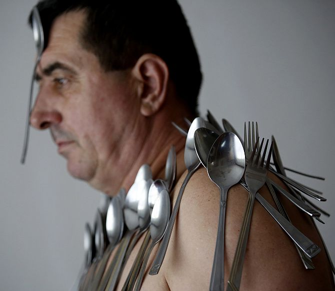 Muhibija Buljubasic, 56, poses for photo with cutlery on his body and head in Srebrenik