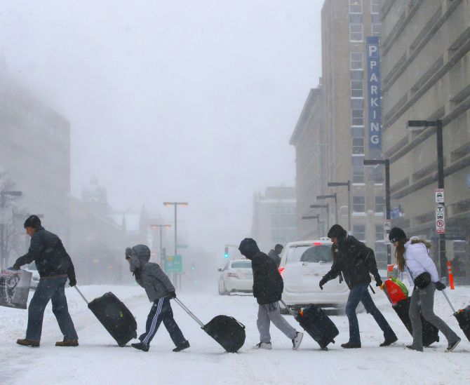 Travelers leave the Back Bay subway station during a winter nor'easter snow storm in Boston, Massachusetts on Friday