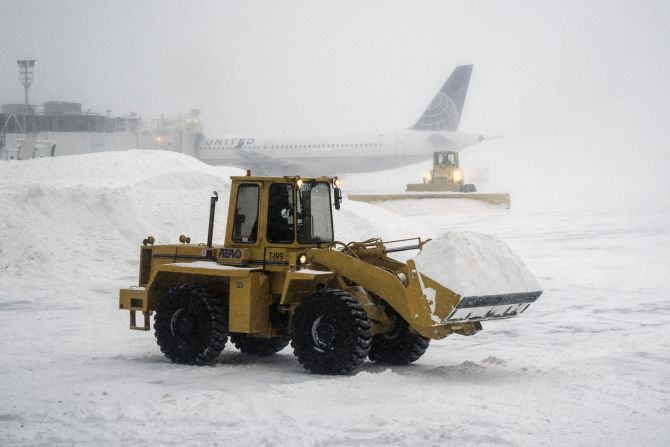 Heavy machinery clears the snow at LaGuardia Airport during a winter storm in New York, on Friday