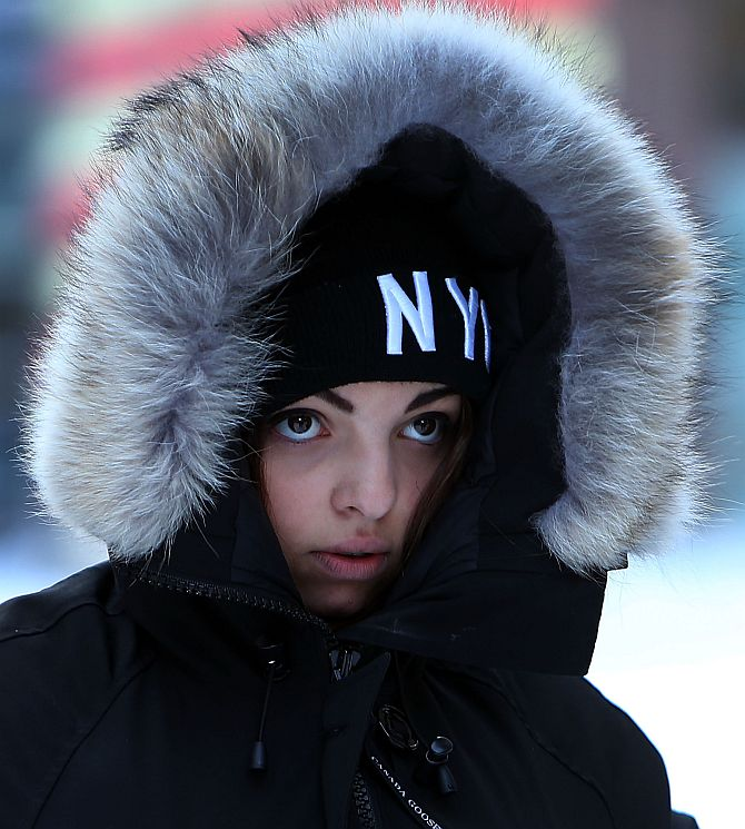 A woman walks through a cold and snow covered Times Square following a snow storm that left up to 8 inches of snow