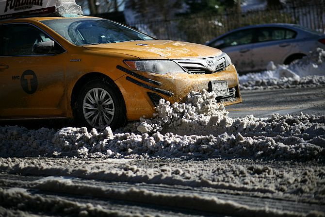 A taxi cab drives into a pile of snow on East End Ave. near E. 86th St. after an overnight storm dropped up to 7 inches of snow