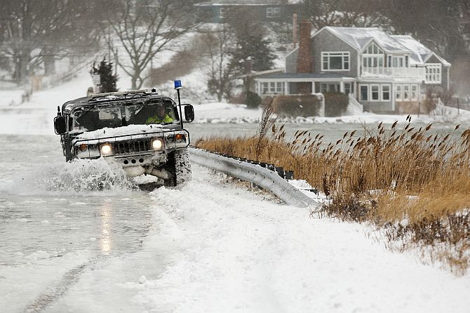 A police vehicle drives through a flooded street during a winter nor'easter snow storm in Scituate, Massachusetts