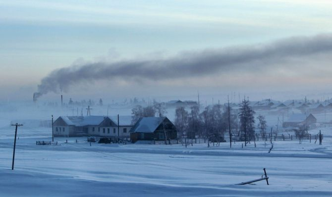 Smoke rises above houses in the village of Maralayi, in the Republic of Sakha, northeast Russia. The coldest temperatures in the northern hemisphere have been recorded in Sakha, the location of the Oymyakon valley,