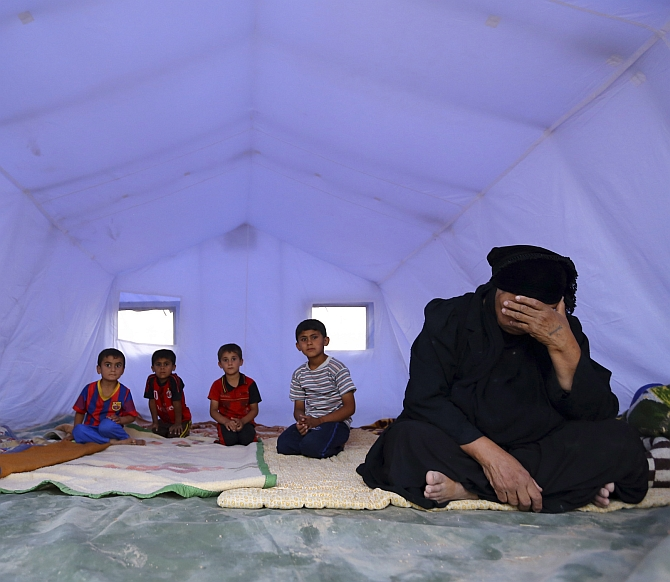 A family, who fled from the violence in Mosul, sits inside a tent at a camp on the outskirts of Arbil in Iraq's Kurdistan region