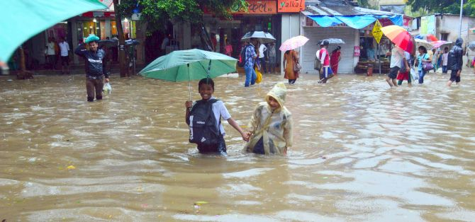 Little children wade through knee-high water after rains lashed the city.