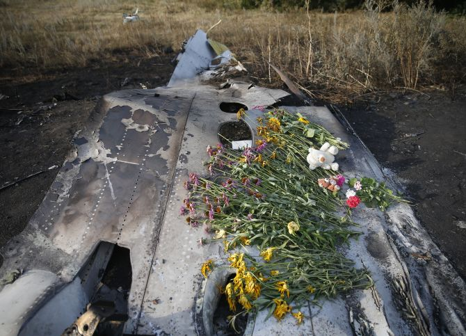 Flowers and mementos lie on wreckage at the crash site of Malaysia Airlines Flight MH17, near the settlement of Grabovo in the Donetsk.