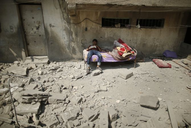 A wounded Palestinian sits against a residential building where he lives, which police said was destroyed in an Israeli air strike, in Gaza City