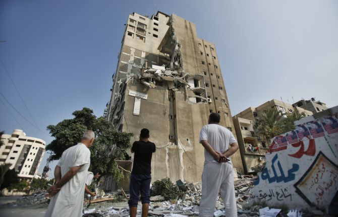 Palestinians look at a residential building which police said was hit in an Israeli air strike
